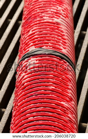 Old red pipe with black tape connection on grate.