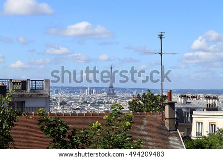 Old red roof and maple tree view with Eiffel Tower at the background on summer day