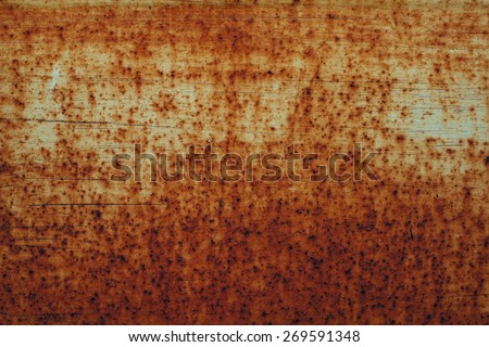 Old red rusty metal plate heavily aged and corroded. The corrosion stain creates a grungy frame. Metal corroded texture and background - stock photo