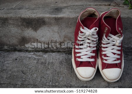 Old Red Sneakers on cement blackground