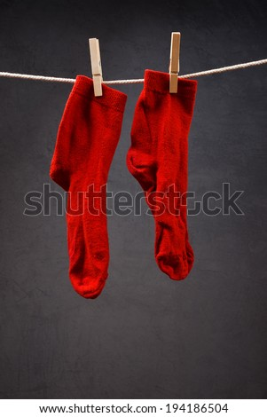 Old red socks hanging on rope attached with clothespins to dry. - stock photo