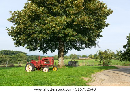 Old red tractor at the farm - stock photo