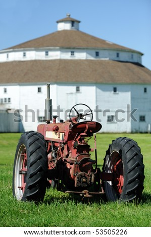 Old red tractor in front of round barn - stock photo