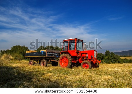 Old red tractor on the agricultural field in autumn