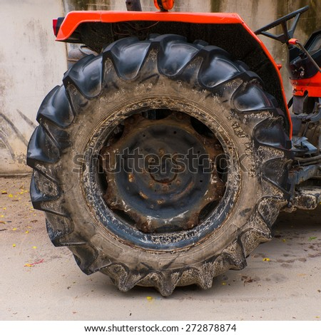 old red tractor wheel - stock photo