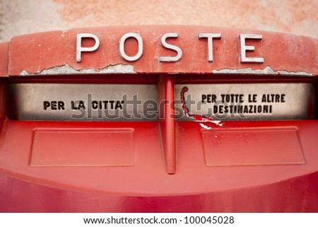 Old red vintage retro mailbox in italy - stock photo
