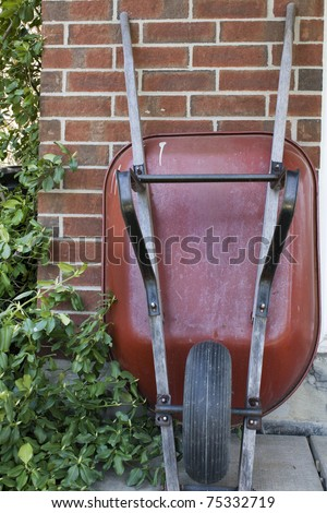 Old, red wheelbarrow propped up against a brick wall