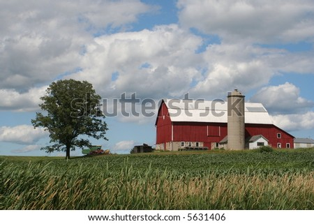 old red Wisconsin dairy barn on hill - stock photo