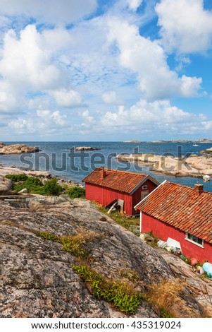 Old red wooden cottages by the sea - stock photo