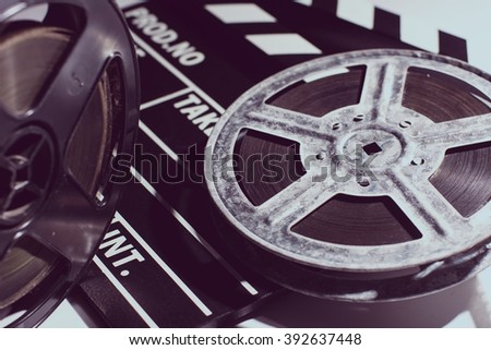 Old reel of film and cinema clap lying on a light table. Toned image - stock photo