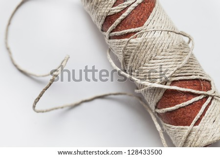 old reel of thread on a white background, the twine on a spool - stock photo
