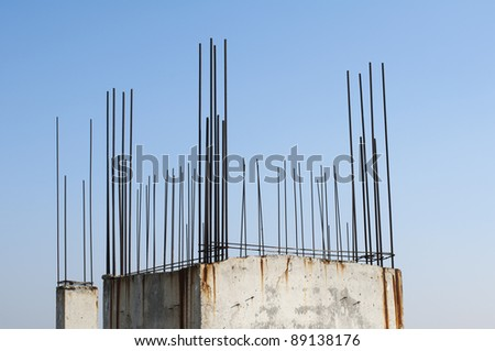 Old reinforcing steel protruding from the concrete. Blue sky background