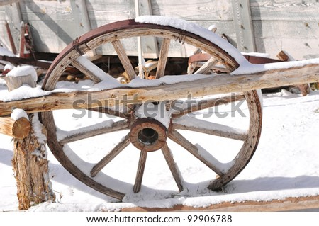 Old restored wagon wheel in early season snowstorm - stock photo