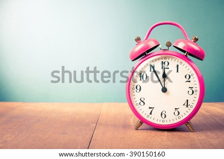 Old retro alarm clock on table. Vintage style filtered photo - stock photo