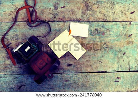 Old retro camera on vintage wooden background - stock photo