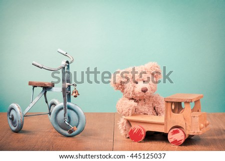 Old retro children's toys: bicycle, Teddy Bear, wooden car. Vintage instagram style filtered photo