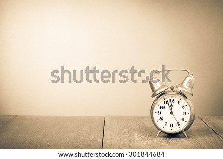 Old retro clock on table. Vintage style sepia photo - stock photo