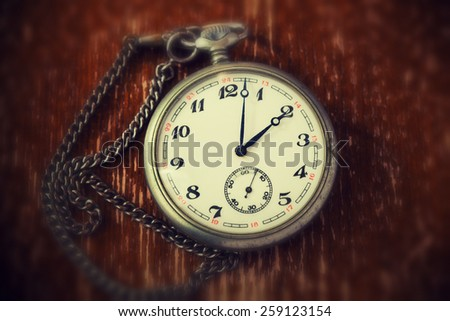 Old retro clock on vintage background - stock photo
