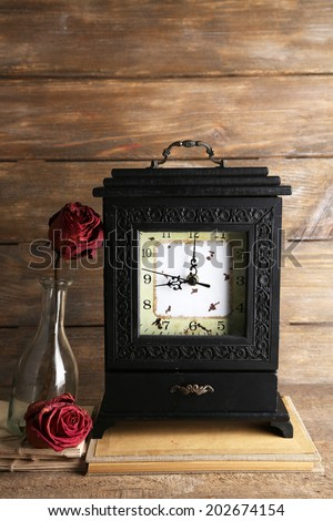 Old retro clock on wooden background - stock photo