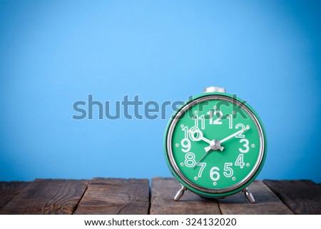 Old retro clock on wooden table with blue background still life with copy space - stock photo