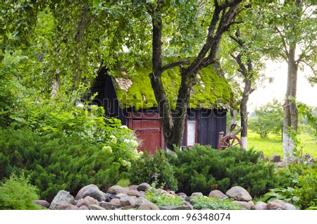 Old retro garden house mossy roof in park surrounded by plants and flowers background. Romantic view.