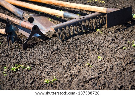 Old retro garden tools (cultivator, shovel, rake) over brown soil (ploughed land) close up. Copy space. Agriculture, gardening, soil cultivation concept. - stock photo