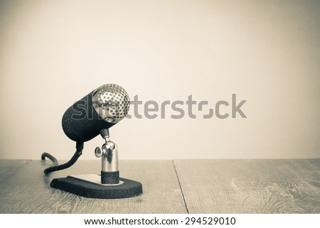 Old retro microphone from 50s on table. Vintage style sepia photo - stock photo