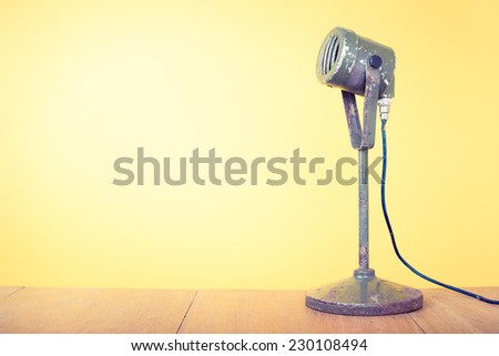 Old retro microphone front yellow background - stock photo