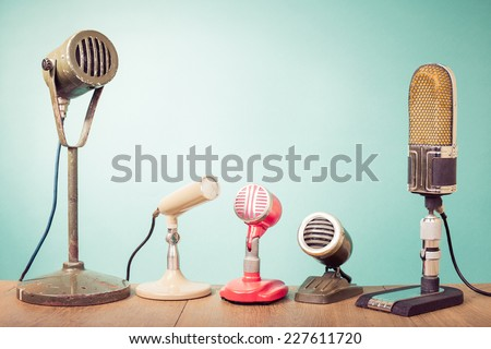 Old retro microphones for press conference or interview front mint green wall background - stock photo