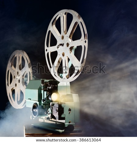 Old retro movie projector with smoke and light beam - stock photo