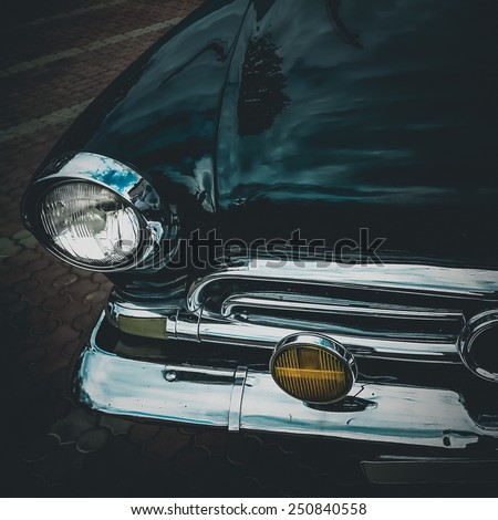 Old retro or vintage car or automobile front side with front lights or headlights and radiator grill. Processed by vintage or retro effect filter