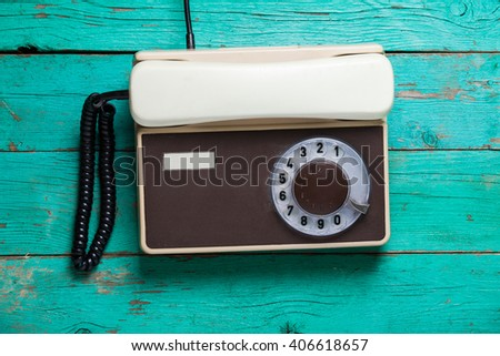 Old retro phone on wooden board, top view