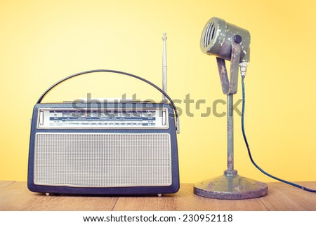 Old retro radio and microphone front yellow background - stock photo