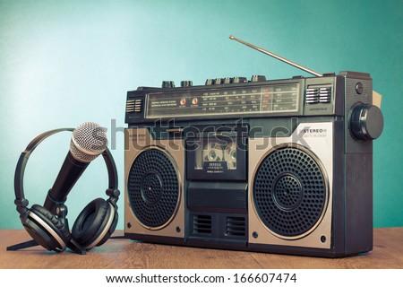 Old retro radio cassette player, headphones, microphone on table - stock photo