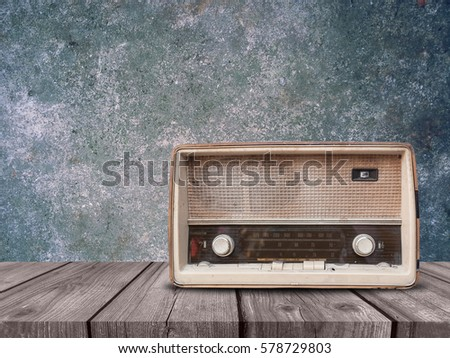 Old retro radio on wood table with concrete background
