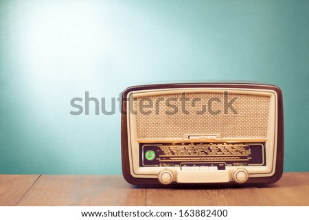 Old retro radio with green eye light on table front gradient background - stock photo