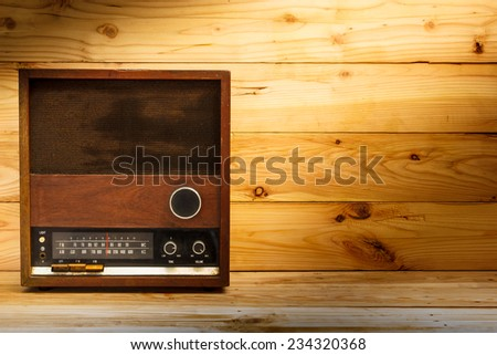 old retro radio with light on wood table. - stock photo