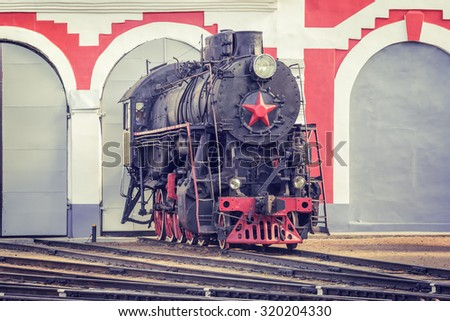 Old retro steam locomotive stands by the gates of the depot. - stock photo