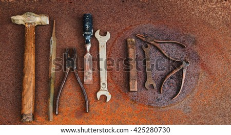 Old retro steel tools, bench's or carpenter's instruments, on rusty metal background. Hammer, wrenches, pliers. Top view. - stock photo