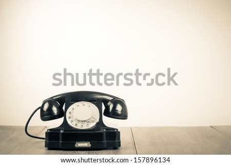 Old retro telephone on table sepia photo - stock photo