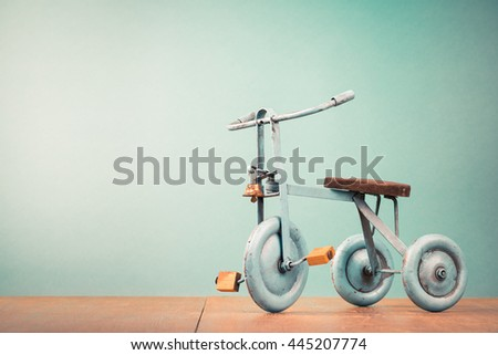 Old retro toy bicycle with three wheels. Vintage instagram style filtered photo - stock photo
