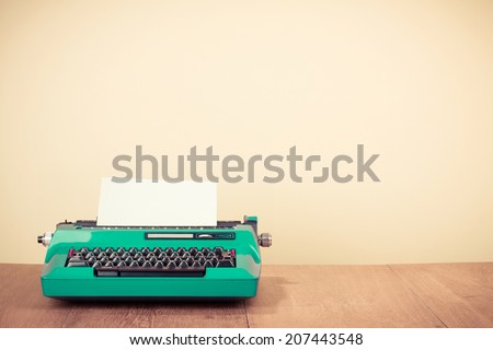 Old retro typewriter on wooden desk - stock photo