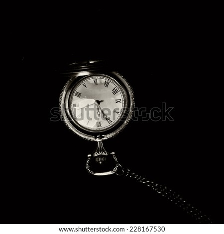 Old retro watch over black showing five to midnight (monochrome toning) - stock photo