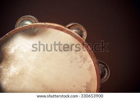 Old retro wooden tambourine on brown background, closeup view of details.  - stock photo