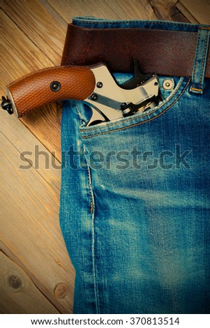 old revolver in the pocket of vintage blue jeans. instagram image filter retro style - stock photo