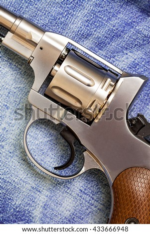 old revolver on blue jeans background, close-up - stock photo