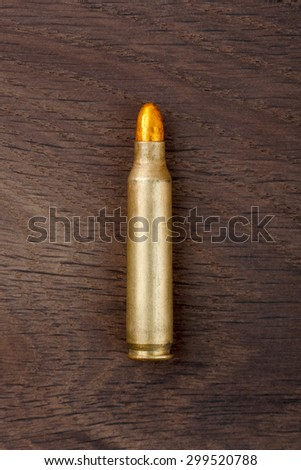 Old rifle bullet on the old wooden desk. - stock photo