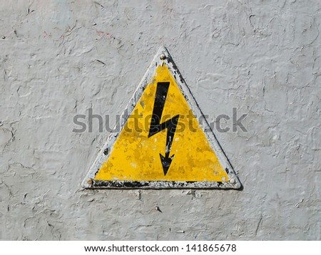 Old risk of electric shock triangle sign on light grey weathered cracked background - stock photo