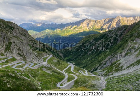 Old road with tight serpentines on the southern side of the St. Gotthard pass bridging swiss alps at sunset in Switzerland, europe