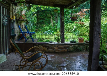 old rocking chair in a tranquil garden - stock photo